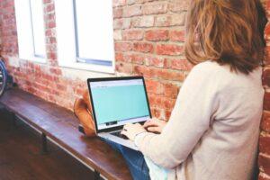 femme assise avec son ordinateur portable sur les genous