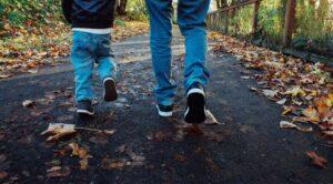 Photo d'un papa et son fils en train de marcher sur une route