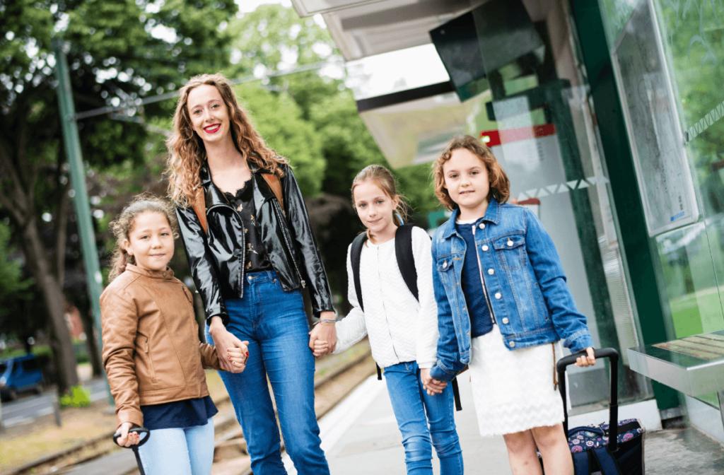 Une adulte qui accompagne les enfants à l'école