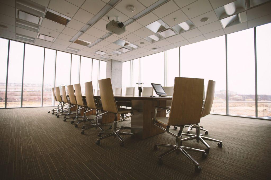 Grande salle de réunion avec une grande table en bois au milieu bordée de grandes vitres