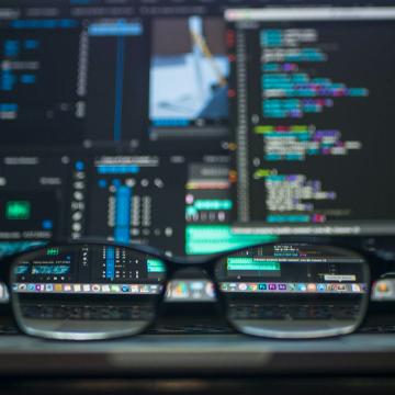 Un zoom photo sur des lunettes posées sur le clavier d'un développeur avec des lignes de codes en fond d'écran