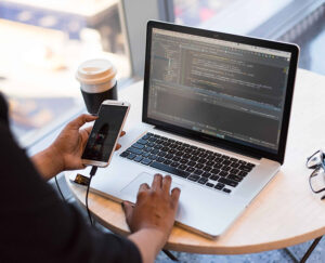 Photo qui représente l'agilité d'une personne en train de coder et de vérifier sur mobile le résultat