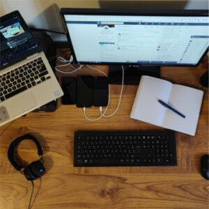 Bureau d'un collaborateur super connecté avec son ordinateur branché sur son ordinateur portable et son téléphone, un bloc note posé sur son bureau.