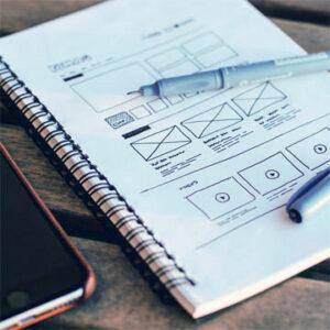Un carnet de note avec un croquis fait à la main pour représenter un parcours utilisateur