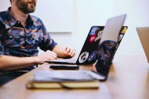Un homme assied à côté d'un bureau avec son ordinateur portable ouvert devant lui